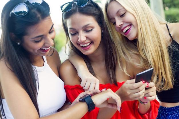 d9ad8d17a05 Drie meiden chatten met hun smartphones in het park. Foto   Gratis ...
