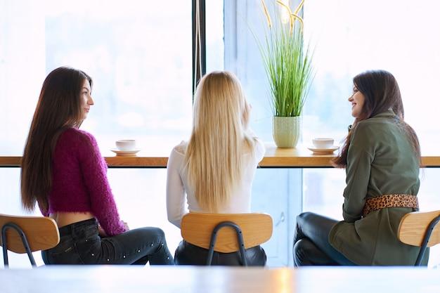 Drie meisjes hebben een gesprek in café tijdens theetijd. Premium Foto