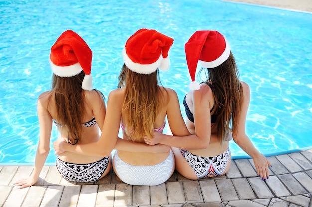 Drie meisjes in badpakken en kappen van de kerstman op een poolachtergrond Premium Foto