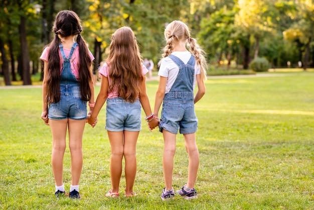 Drie meisjes lopen weg achteruit Gratis Foto