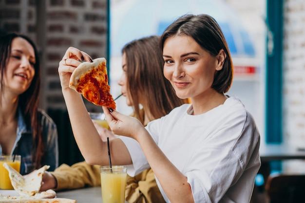 Drie meisjesvrienden die pizza hebben bij een bar Gratis Foto
