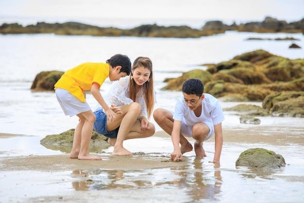 Drie mensen aziatische familie, moeder en zonen, die op tropisch strand spelen Premium Foto