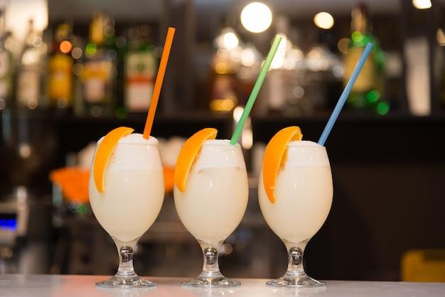 Drie milkshakes met sinaasappel en riet staan op de bar Premium Foto