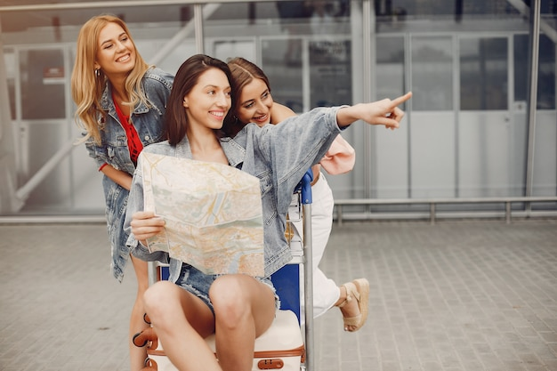Drie mooie meisjes die zich bij de luchthaven bevinden Gratis Foto