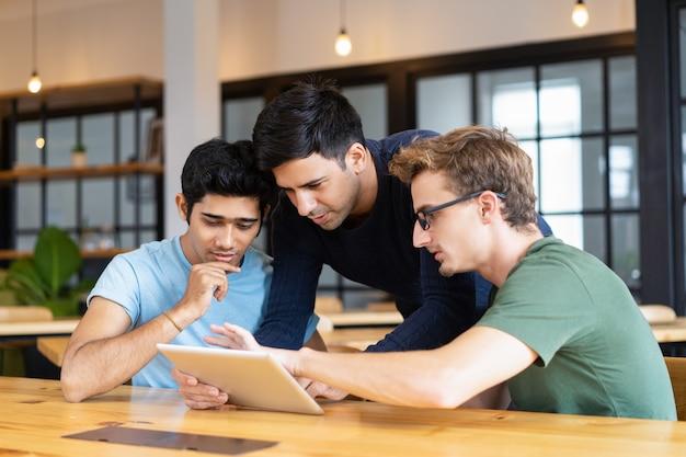 Drie nadenkende studenten die tabletcomputer met behulp van Gratis Foto