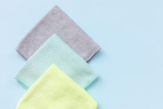 Drie nieuwe gevouwen microfiber doek voor het reinigen over de blauwe achtergrond. handdoeken van microweefsel reinigen voor afstoffen en polijsten. huishoudelijke schoonmaak concept. close-up, kopieer ruimte Premium Foto