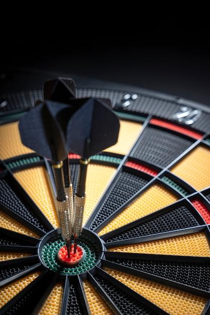 Drie pijltjes in bullseye van dartboard Premium Foto