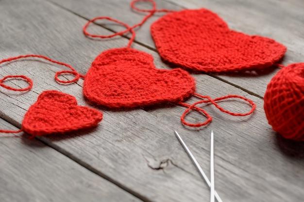 Drie rode gebreide harten, die liefde en familie symboliseren. familierelatie, obligaties. Premium Foto