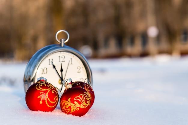 Drie rode kerstballen en wath op sneeuw Premium Foto