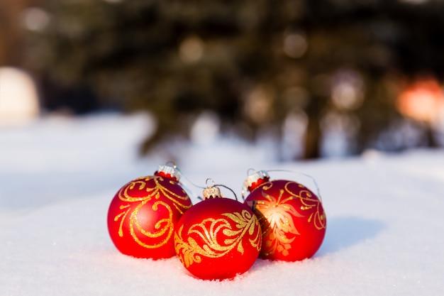 Drie rode kerstballen op een sneeuw. nieuwjaar wenskaart concept. copy-ruimte Premium Foto