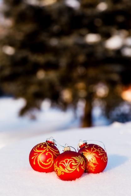 Drie rode kerstballen op sneeuw Premium Foto