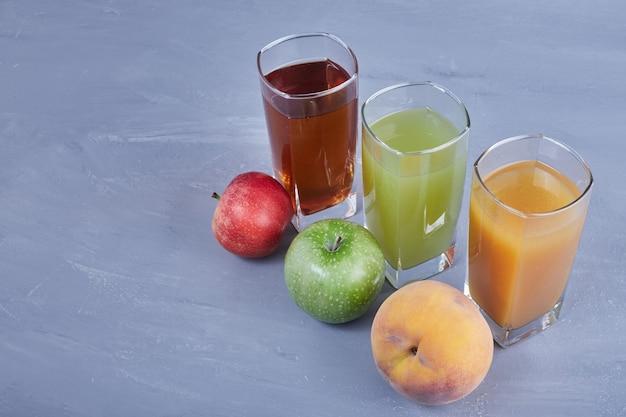 Drie soorten fruit met glazen sappen. Gratis Foto
