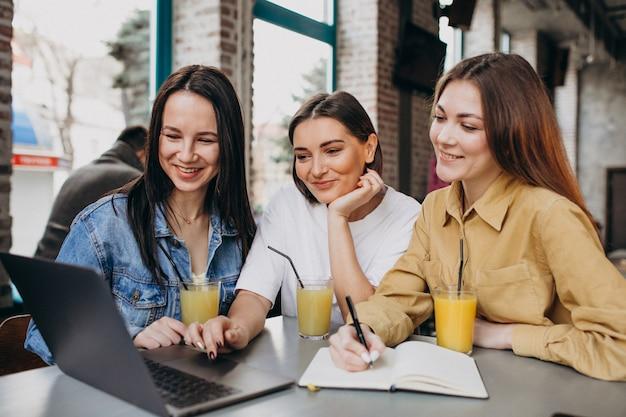Drie studenten examen voorbereiden met laptop in een café Gratis Foto