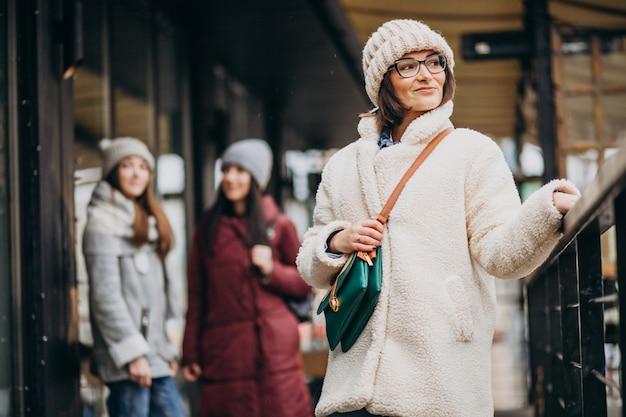 Drie studenten in de winter outfit op straat Gratis Foto