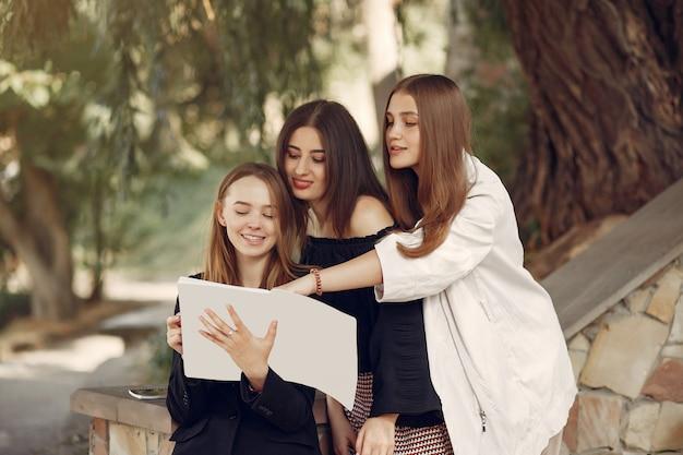 Drie studenten staan in een universiteitscampus Gratis Foto
