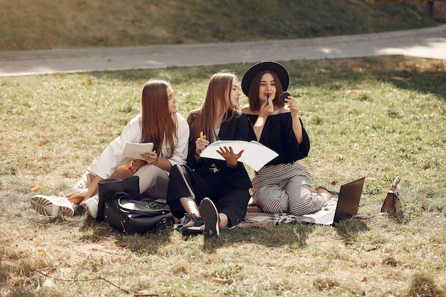 Drie studenten zitten op een gras met laptop Gratis Foto