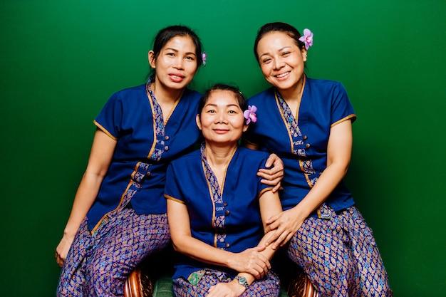Drie thaise etnische, gelukkige, glimlachende masseurs personeel van het hotelpersoneel met orchideebloem in haarportret in traditionele oosterse exotische kuuroordkostuums die camera bekijken Premium Foto