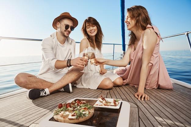 Drie trendy europese vrienden zitten op de boot, lunchen en drinken champagne, uiting geven aan vreugde en plezier. elk jaar boeken ze in de winter kaartjes voor warme landen Gratis Foto