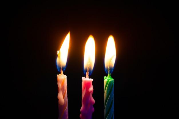 Drie verjaardagskaarsen op zwart Premium Foto