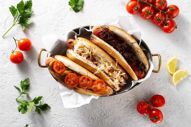 Drie verschillende hotdoggrills dienden in een pan op een lichte achtergrond, hoogste mening Premium Foto