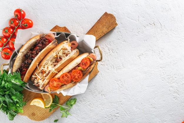 Drie verschillende hotdoggrills dienden in pan op een houten raad op lichte achtergrond. kopieer ruimte bovenaanzicht Premium Foto