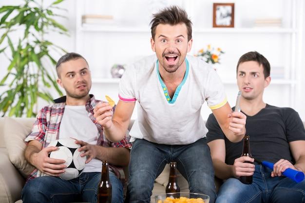Drie voetbalfans juichen thuis voetbalwedstrijd toe. Premium Foto