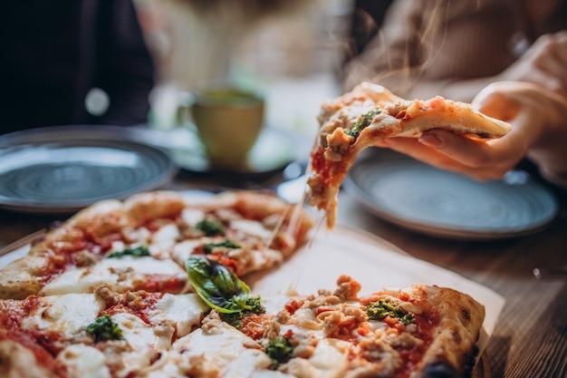 Drie vrienden die samen pizza eten in een café Gratis Foto