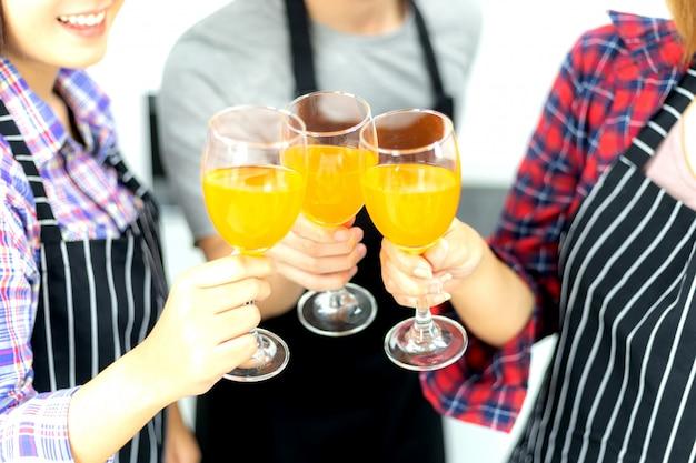 Drie vrienden die van het glas van de partij genieten, die jus d'orangecocktail samen drinken Premium Foto