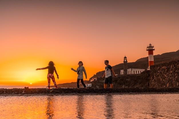 Drie vrienden in de oranje zonsondergang op de zoutvlakten en op de achtergrond de fuencaliente-vuurtoren op de route van de vulkanen ten zuiden van het eiland la palma, canarische eilanden, spanje Premium Foto