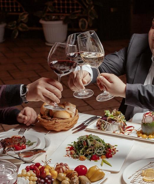 Drie vrienden juichen wijnglazen met rode en witte wijn toe tijdens het diner Gratis Foto