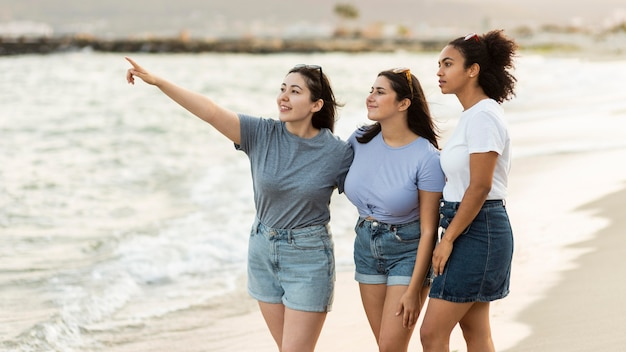 Drie vriendinnen die het uitzicht op het strand bewonderen Gratis Foto
