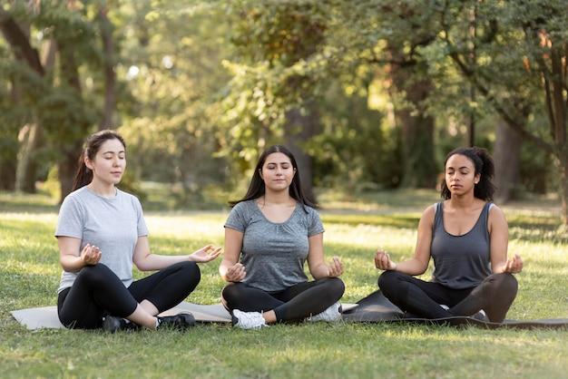 Drie vriendinnen doen yoga in het park Gratis Foto