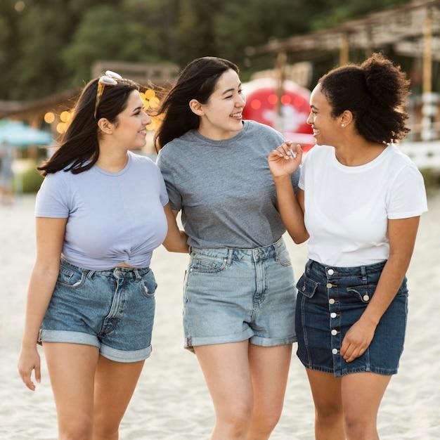 Drie vriendinnen met plezier op het strand Gratis Foto