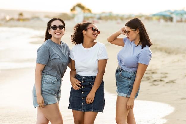 Drie vriendinnen met zonnebril op het strand Premium Foto