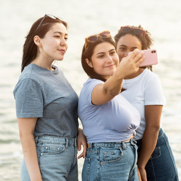 Drie vriendinnen nemen selfie op het strand Premium Foto