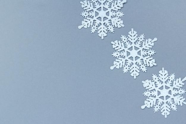 Drie witte decoratieve sneeuwvlokken op een grijze achtergrond. kerstmis en nieuwjaar, een plek voor tekst, minimalisme, winterachtergrond Premium Foto