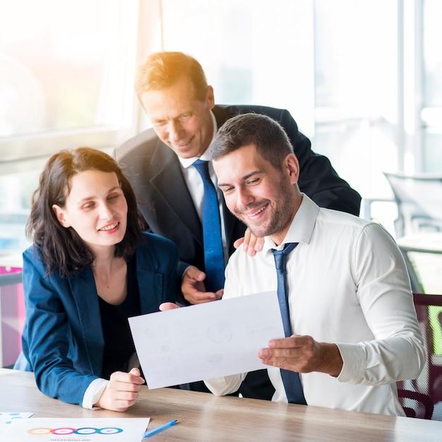 Drie zakenlui die bedrijfsrapport in het bureau bekijken Gratis Foto