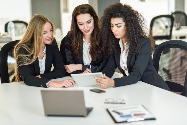 Drie zakenvrouwen die samenwerken in een modern kantoor Gratis Foto