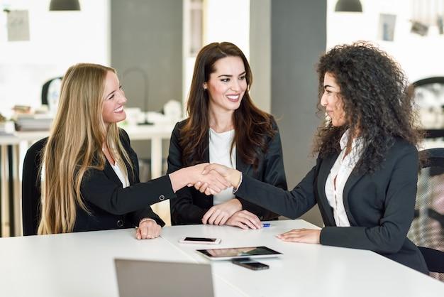 Drie zakenvrouwen schudden handen in een modern kantoor Gratis Foto