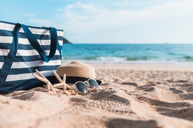 Drie zeesterren met blauwe zak op zand Gratis Foto