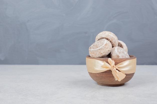 Drie zoete koekjes met gouden boog op houten kom Gratis Foto