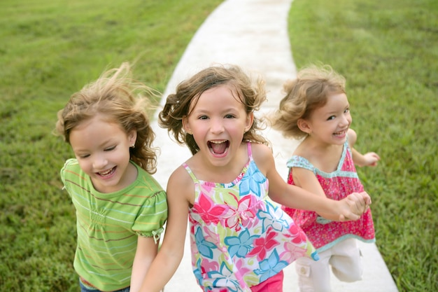 Drie zustermeisjes spelen op het park Premium Foto