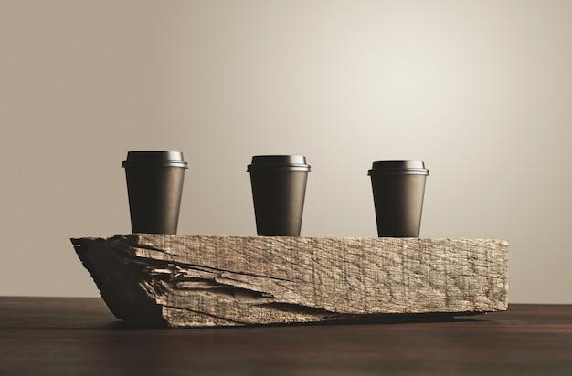Drie zwarte afhaalmaaltijden papieren bekers met gesloten doppen geïsoleerd op houten steen op tafel Gratis Foto