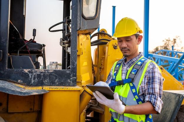 Drijvende werker met zware banden, werknemers drijven bestellingen door de tablet, wiellader graafmachine met graaflaadmachine die zand op de bouwplaats lost. Premium Foto