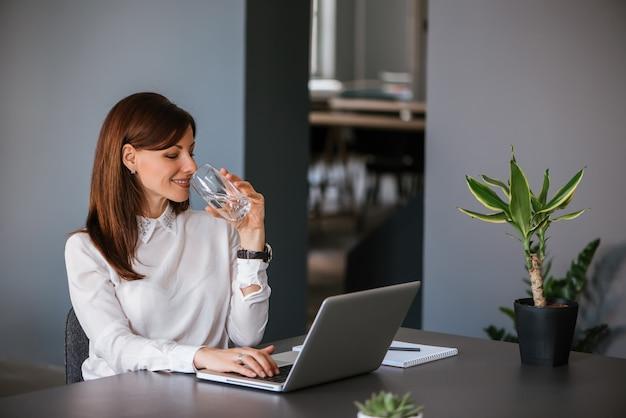 Drinkwater tijdens het werken met een laptop Premium Foto