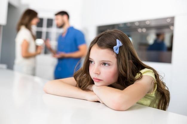 Droevig meisje dat op lijst tegen ruzieouders leunt Premium Foto