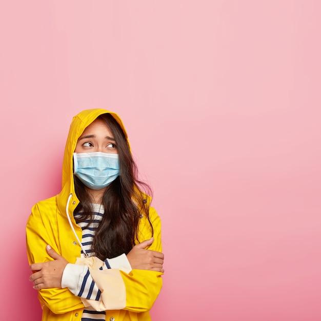 Droevige bezorgde koreaanse vrouw verkouden na een wandeling tijdens koud regenachtig weer, houdt de handen gekruist Gratis Foto