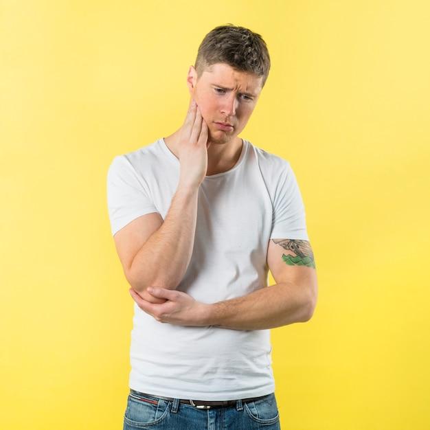 Droevige jonge mens die tandpijn heeft tegen gele achtergrond Gratis Foto