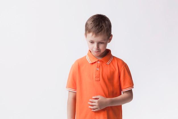 Droevige kleine jongen die zich dichtbij witte muur bevindt die maagpijn heeft Gratis Foto