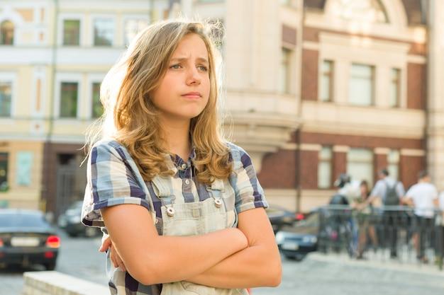 Droevige meisjestiener met wapens die op een stadsstraat worden gekruist Premium Foto